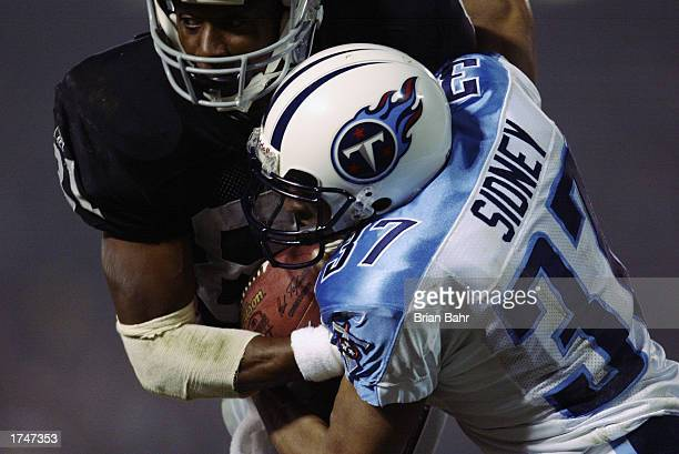 Wide receiver Tim Brown of the Oakland Raiders holds onto the ball after the reception against cornerback Dainon Sidney of the Tennessee Titans...