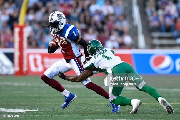 Wide receiver Tiquan Underwood of the Montreal Alouettes runs with the ball against defensive back Jovon Johnson of the Saskatchewan Roughriders...