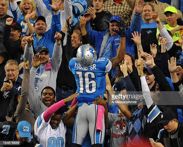 Wide receiver Titus Young of the Detroit Lions jumps into the stands to celebrate a touchdown catch in the second quarter against the Seattle...