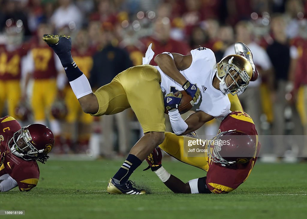 Wide receiver TJ Jones #7 of the Notre Dame Fighting Irish is brought down by linebacker Lamar Dawson #55 of the USC Trojans in the first half at Los Angeles Memorial Coliseum on November 24, 2012 in Los Angeles, California. Notre Dame defeated USC Trojans 22-13.