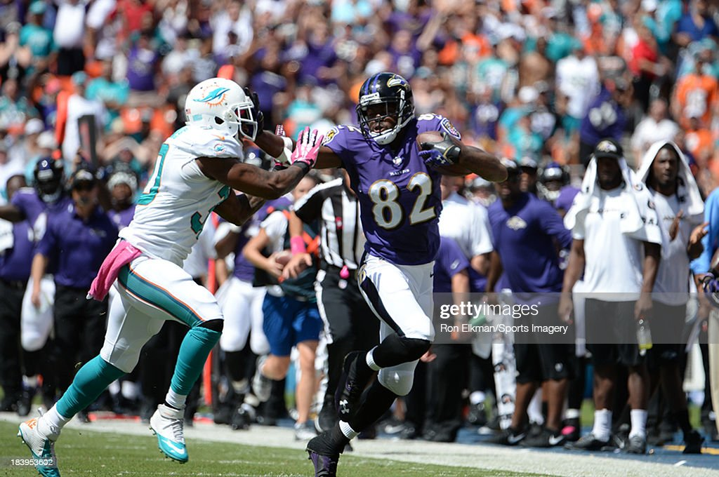 Wide receiver <a gi-track='captionPersonalityLinkClicked' href=/galleries/search?phrase=Torrey+Smith&family=editorial&specificpeople=5527843 ng-click='$event.stopPropagation()'>Torrey Smith</a> #82 of the Baltimore Ravens carries the ball as safety Chris Clemons #30 of the Miami Dolphins tries to tackle him during a NFL game at Sun Life Stadium on October 6, 2013 in Miami Gardens, Florida.