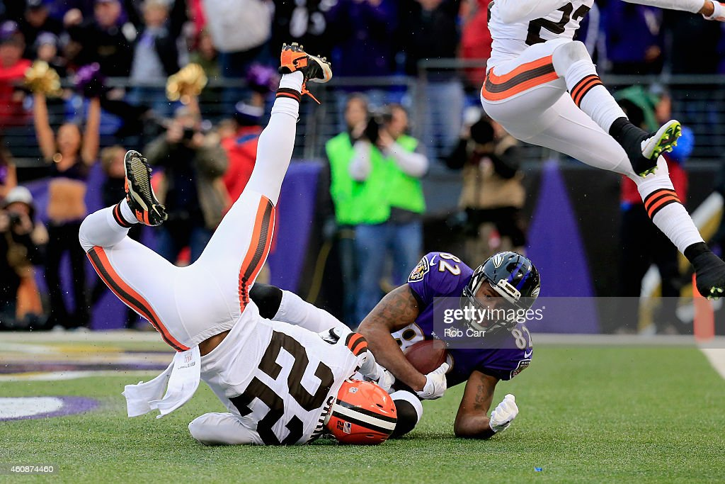Wide receiver Torrey Smith #82 of the Baltimore Ravens catches a fourth quarter touchdown pass over the defense cornerback Buster Skrine #22 of the Cleveland Browns at M&T Bank Stadium on December 28, 2014 in Baltimore, Maryland.