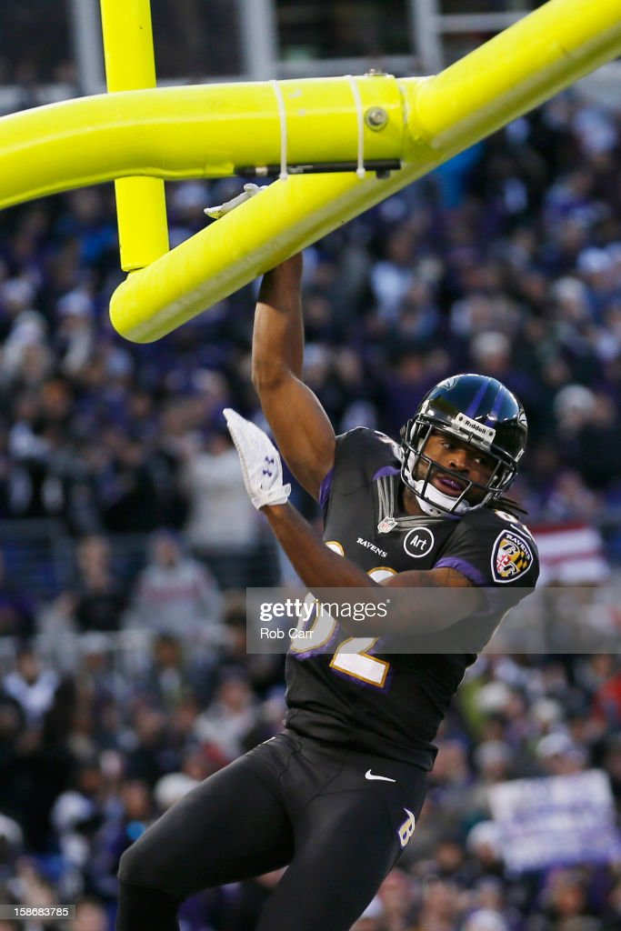 Wide receiver Torrey Smith of the Baltimore Ravens hangs on the goal post after catching a touchdown pass during the first quarter against the New...