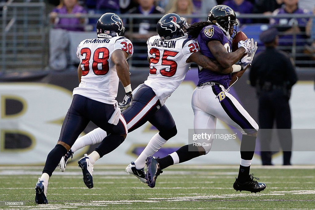 Wide Receiver Torrey Smith #82 of the Baltimore Ravens makes a catch in front of Kareem Jackson #25 of the Houston Texans and Danieal Manning #38 at M&T Bank Stadium on October 16, 2011 in Baltimore, Maryland.