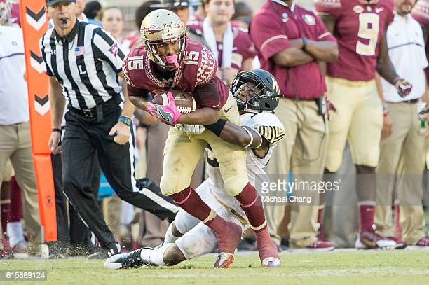 Wide receiver Travis Rudolph of the Florida State Seminoles attempts to escape a tackle by defensive back Essang Bassey of the Wake Forest Demon...