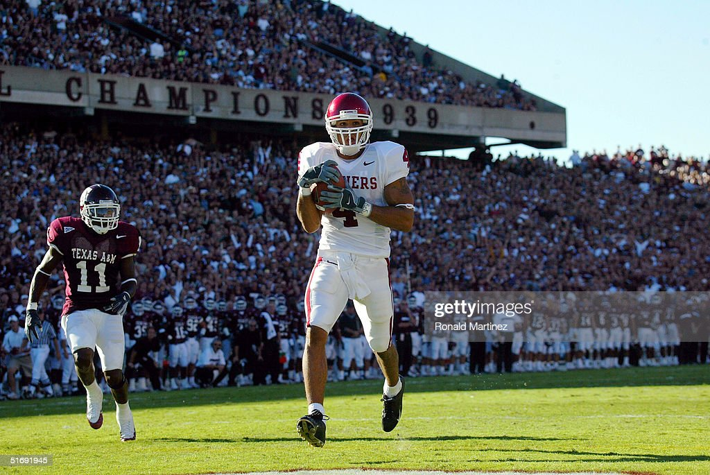 Wide receiver Travis Wilson #4 of the University of Oklahoma Sooners makes a touchdown pass reception in front of Byron Jones #11 of the Texas A&M University Aggies on November 6, 2004 at Kyle Field in College Station, Texas.