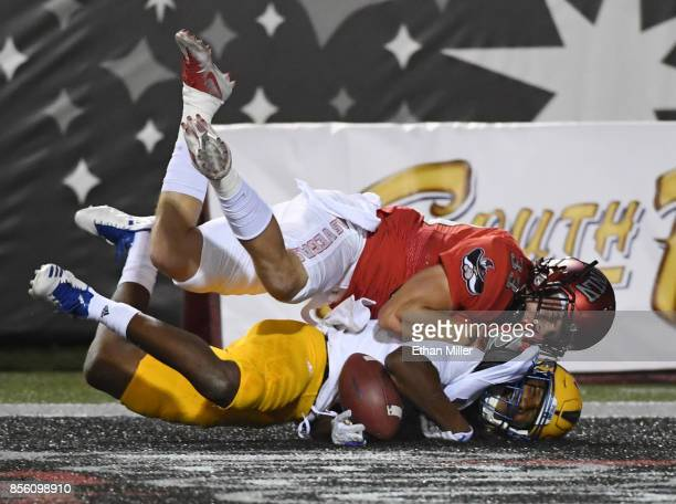 Wide receiver Tre Hartley of the San Jose State Spartans misses a pass in the end zone as he is hit by defensive back Dalton Baker of the UNLV Rebels...