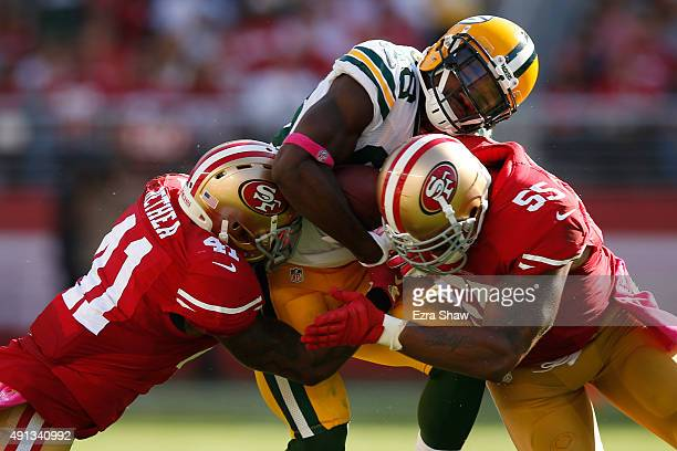 Wide receiver Ty Montgomery of the Green Bay Packers is hit by strong safety Antoine Bethea and outside linebacker Ahmad Brooks of the San Francisco...
