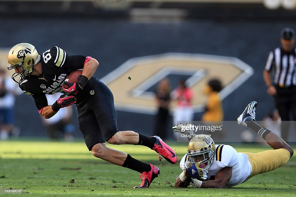 Wide receiver Tyler McCulloch #87 of the Colorado Buffaloes makes a reception and break the tackle of cornerback Aaron Hester #21 of the UCLA Bruins for a 22 yard gain at Folsom Field on September 29, 2012 in Boulder, Colorado. UCLA defeated Colorado 42-14.