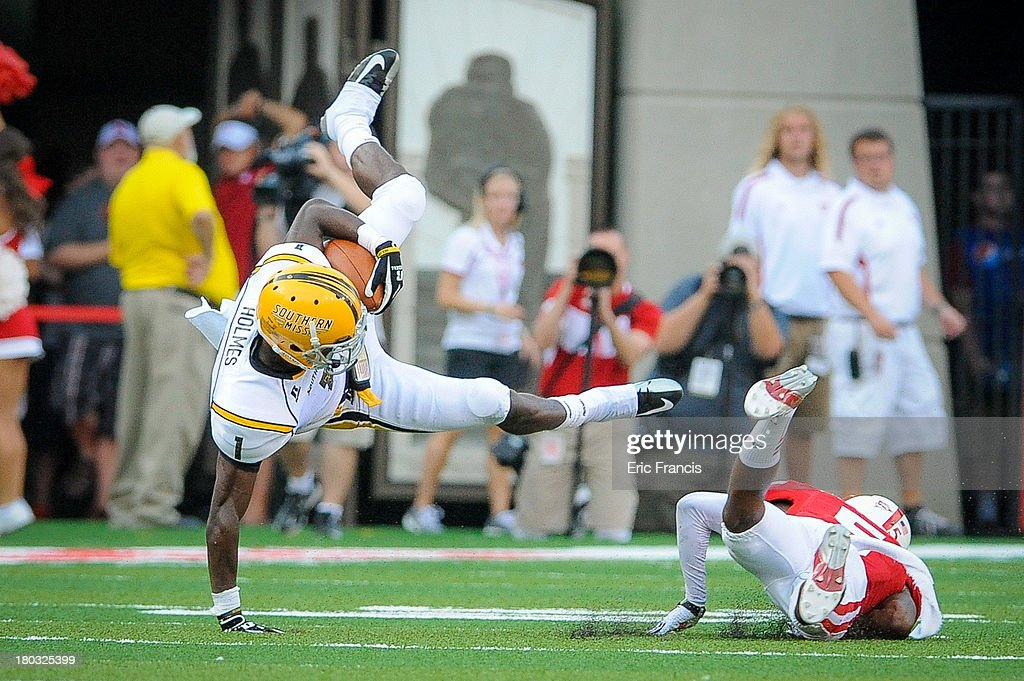 Wide receiver Tyre'oune Holmes #1 of the Southern Miss Golden Eagles is tripped up by cornerback Josh Mitchell #5 of the Nebraska Cornhuskers during their game at Memorial Stadium on September 7, 2013 in Lincoln, Nebraska.