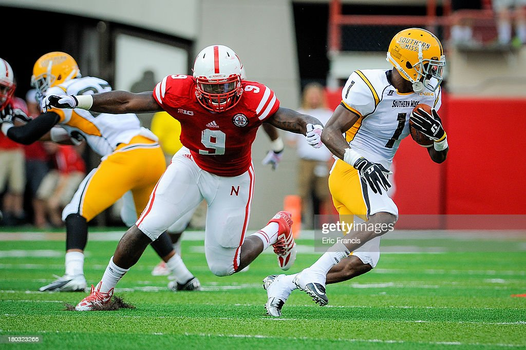 Wide receiver Tyre'oune Holmes #1 of the Southern Miss Golden Eagles runs past linebacker defensive end Jason Ankrah #9 of the Nebraska Cornhuskers during their game at Memorial Stadium on September 7, 2013 in Lincoln, Nebraska.