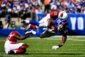 Wide receiver Victor Cruz of the New York Giants is tackled by cornerback Jerraud Powers of the Arizona Cardinals during a game at MetLife Stadium on...