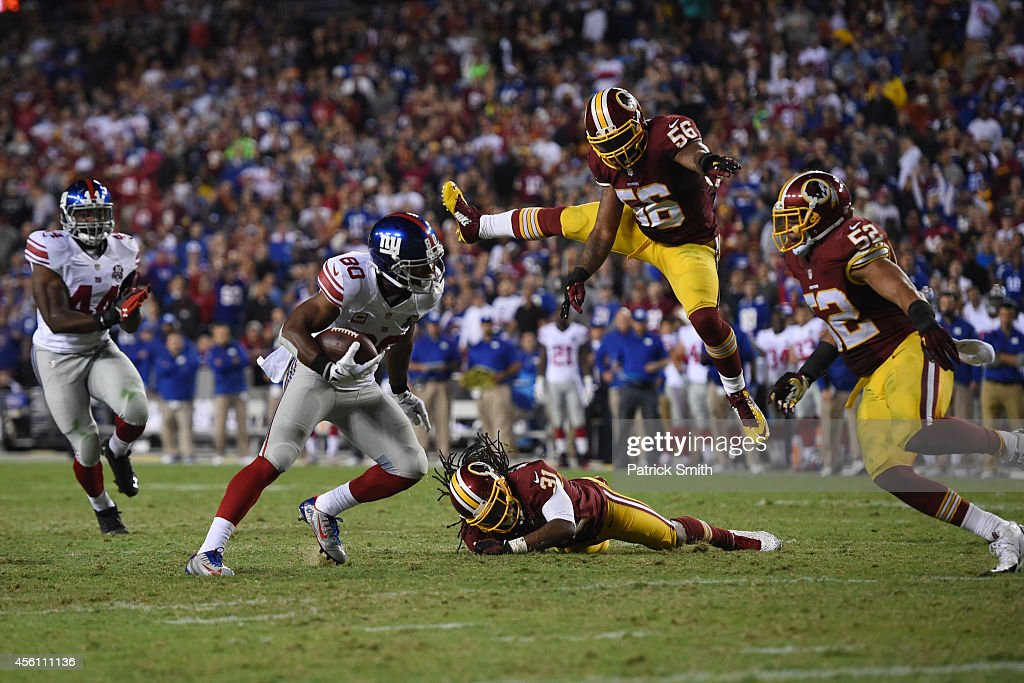 Wide receiver Victor Cruz of the New York Giants runs past inside linebacker Perry Riley of the Washington Redskins during the 3rd quarter of their...