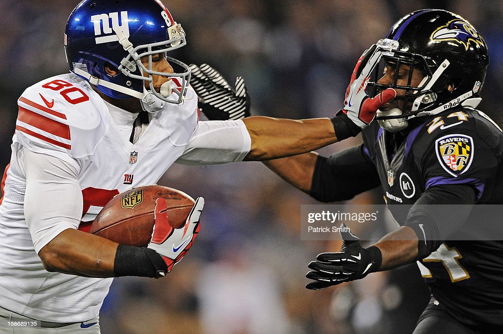 Wide receiver <a gi-track='captionPersonalityLinkClicked' href=/galleries/search?phrase=Victor+Cruz+-+American+Football+Player&family=editorial&specificpeople=8736842 ng-click='$event.stopPropagation()'>Victor Cruz</a> #80 of the New York Giants stiff arms cornerback <a gi-track='captionPersonalityLinkClicked' href=/galleries/search?phrase=Corey+Graham&family=editorial&specificpeople=4294650 ng-click='$event.stopPropagation()'>Corey Graham</a> #24 of the Baltimore Ravens in the third quarter at M&T Bank Stadium on December 23, 2012 in Baltimore, Maryland. The Baltimore Ravens won, 33-14.