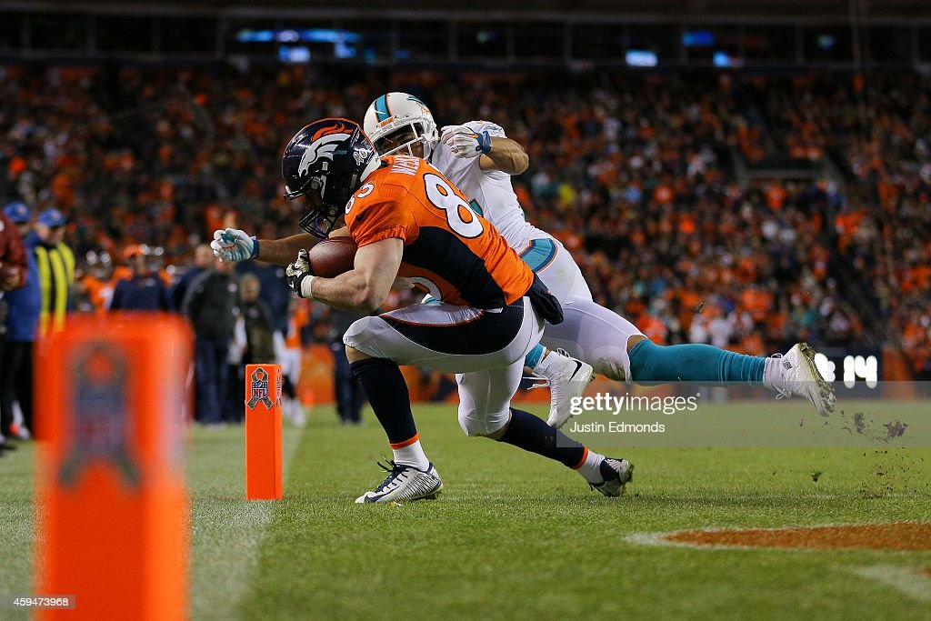 Wide receiver Wes Welker #83 of the Denver Broncos has a fourth quarter touchdown reception under coverage by strong safety Jimmy Wilson #27 of the Miami Dolphins during a game at Sports Authority Field at Mile High on November 23, 2014 in Denver, Colorado.
