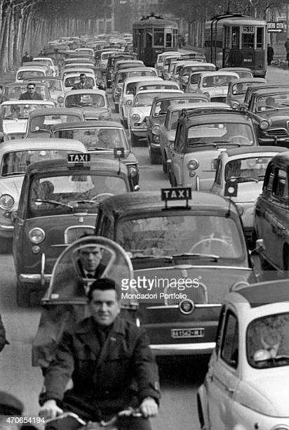 'Wide shot of a congested city street filled with taxis cars and motorscooters in many rows in the closeup a man riding a bicycle in the distance a...