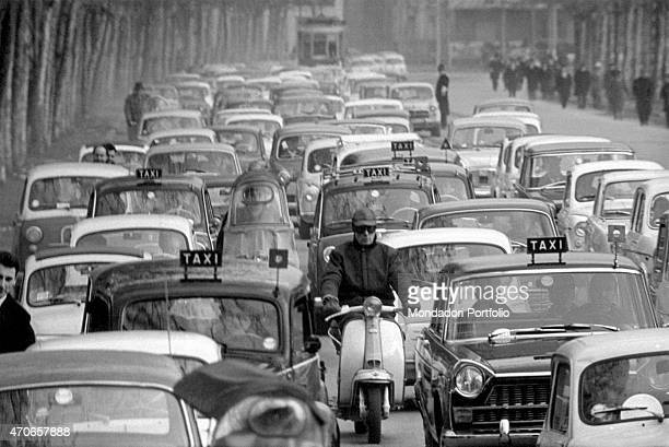 'Wide shot of a congested city street filled with taxis cars and motorscooters in many rows in the distance a tram is coming on the rails Milan 1963 '