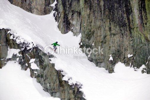 Wide shot of a free skier skiing down a path on a rocky hill.