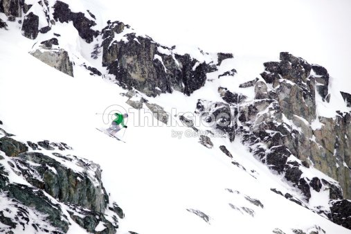 Wide shot of a free skier skiing down a rocky hill.