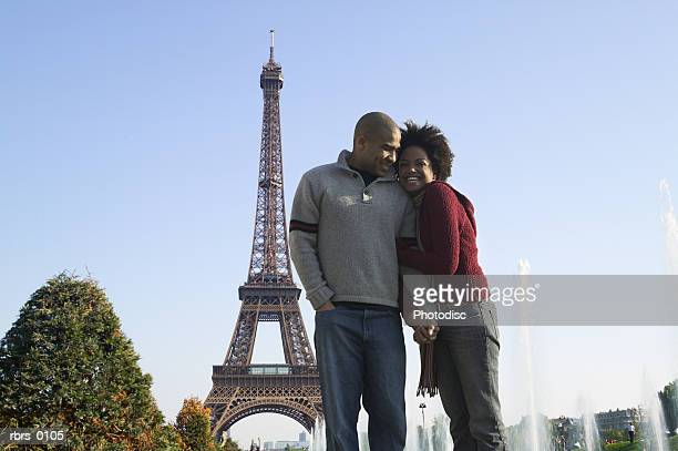 wide shot of a young adult couple as they cuddle together at the eiffel tower in paris