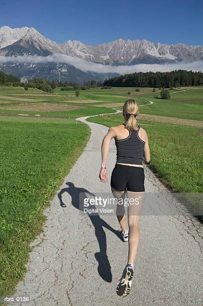 wide shot of a young female jogger as she runs down a long path near a mountain range