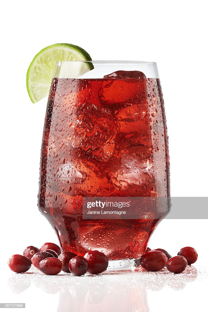 A wide tall glass of fresh cranberry juices served with lime