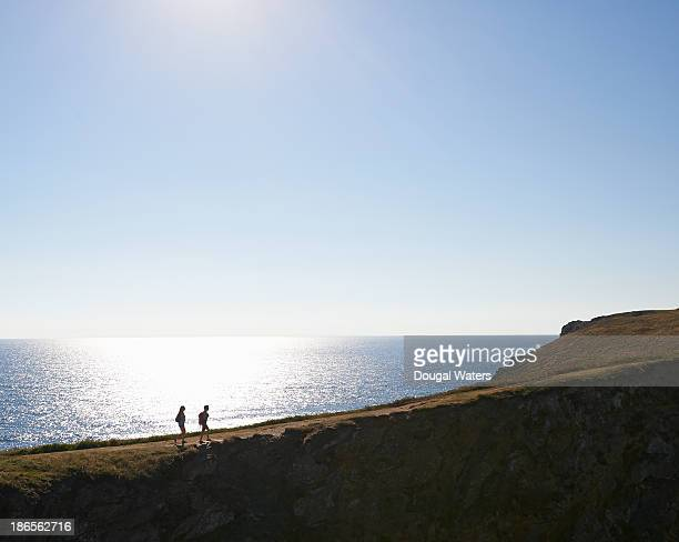 Wide view of couple hiking on UK coastline.