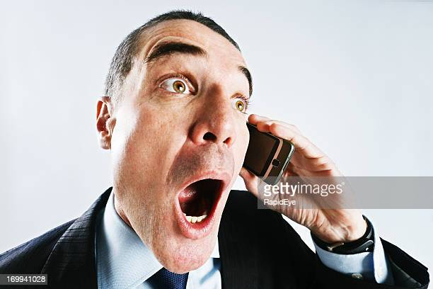 Wide-angle close-up of gasping businessman hearing something on phone