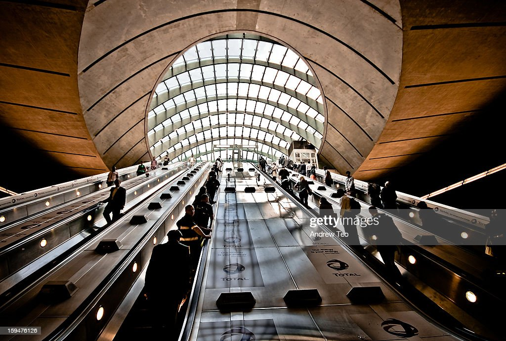 CONTENT] A wide-angle shot of the set of 4 escalators at Canary Wharf underground station in London. Commuters and tourists ascend and descend on the stairways. The naural light entering the shot from the top is shaped by the dome of glass and steel of the walkway cover. The appearance is that of the people heading into the belly of an alien mothership. the shot was taken on a trip to London in the summer of 2009