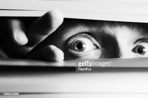 Wide-eyed terrified man peeping though venetian blinds