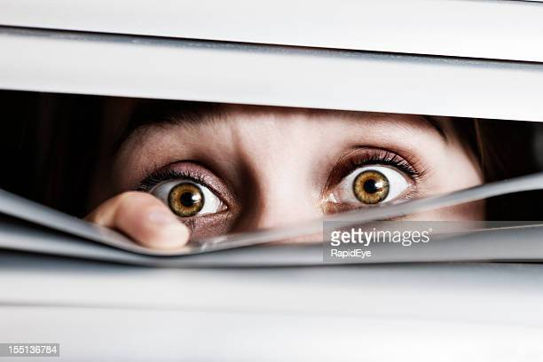 Wide-eyed, terrified young woman looks out through venetian blinds