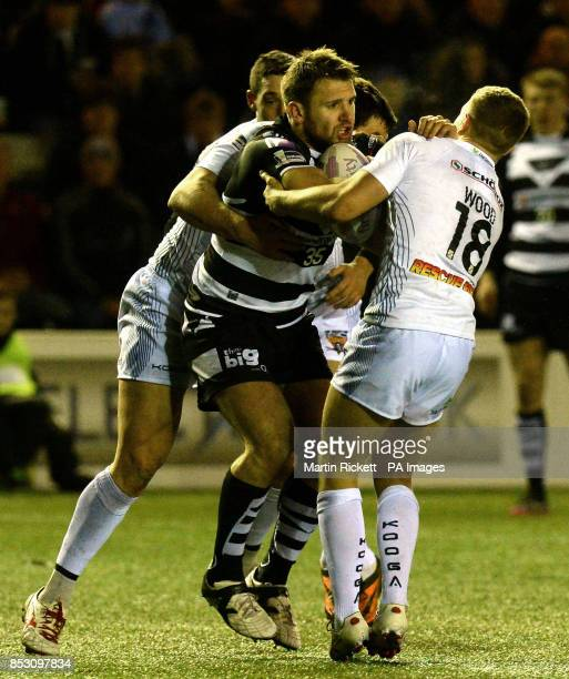 Widnes Vikings Paul Clough is tackled by Huddersfield Giants Brett Ferres and Kyle Wood during the First Utility Super League match at the Select...