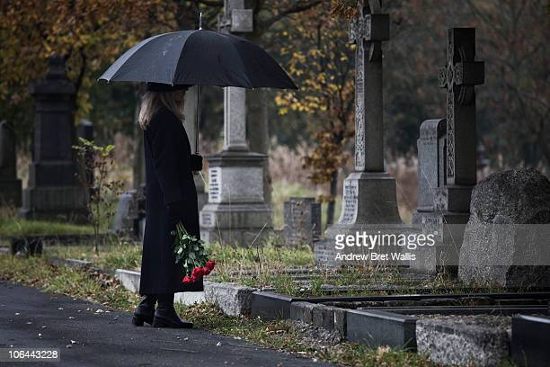 widow bringing roses to a grave in a cemetery