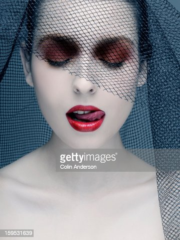 Widow in a black veil licking her lips : Stock Photo