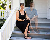 Woman sitting on the steps of her front porch with husband besides her as a sprit to represent that she is a widow.
