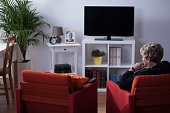 Pensive widow sitting alone in living room