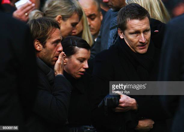 Widow Teresa Enke cries next to manager Joerg Neblung and friend Marco Villa as members of the Hannover 96 football club carry the coffin of their...