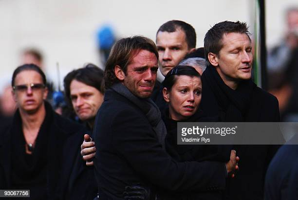 Widow Teresa Enke is supported by manager Joerg Neblung and friend Marco Villa as members of the Hannover 96 football club carry the coffin of their...