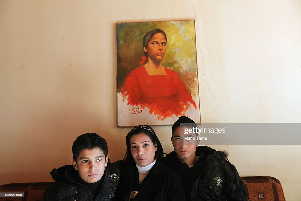 Widow Wafaa Shahab (C) sits with her sons Nooreldin Bassim (R) and Ahmed Bassim on December 12, 2011 in Baghdad, Iraq. Husband and father Bassim Muhammed Muhammed was said to have been executed by al Qaeda militants in front of his house, forcing Shahab and her three children to flee to Syria and northern Iraq for three years. Nooreldin and Ahmed witnessed the killing. A study by Relief International concluded that around10 percent of the approximately 15 million women living in Iraq are widows. A United Nations report estimated that nearly 100 women were widowed daily at the height of the sectarian violence in 2006. Iraq is transitioning nearly nine years after the 2003 U.S. invasion and subsequent occupation. American forces are now in the midst of the final stage of withdrawal from the war-torn country. At least 4,485 U.S. military personnel have died in service in Iraq. According to the Iraq Body Count, more than 100,000 Iraqi civilians have died from war-related violence.