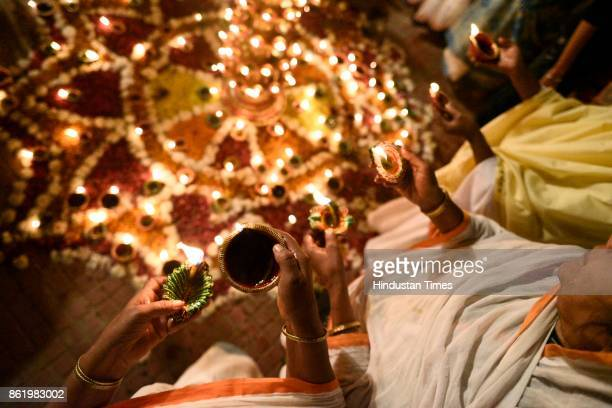 Widows light Diyas and sing religious songs on the eve of Diwali at Gopinath Temple on October 16 2017 in Vrindavan India The event was organised by...