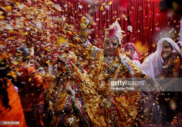 Widows raise their hands as they throw flowers into the air during a holi celebration at the Meera Sahavagini ashram in Vrindavan in the northern...
