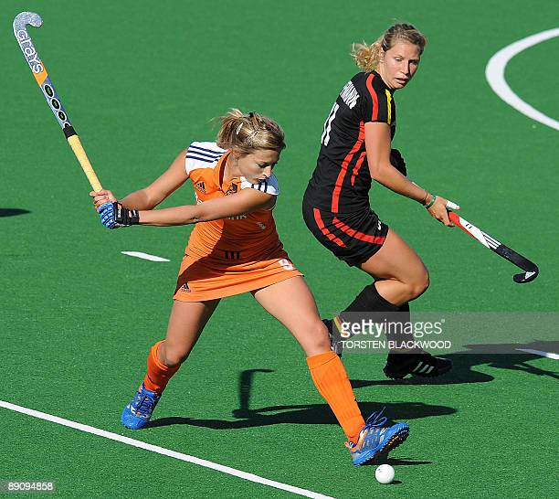 Wieke Dijkstra of The Netherlands hits past Eileen Hoffmann of Germany during the bronze medal playoff for the Women's Hockey Champions Trophy in...