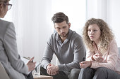 Unhappy wife and husband consulting problem with couple therapist