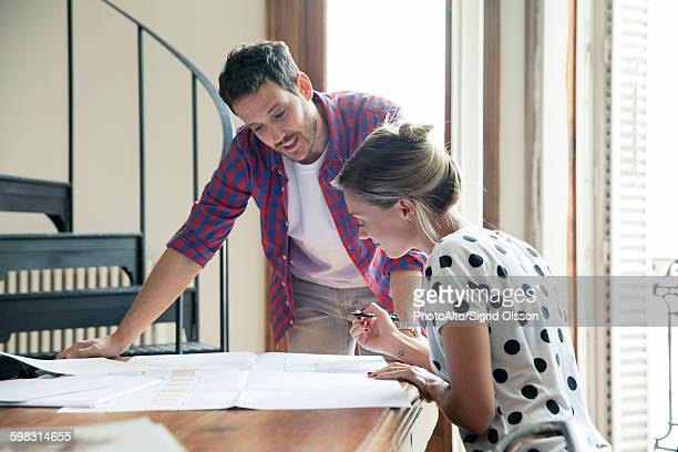 Wife and husband reviewing blueprints for home renovation