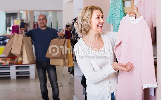 cd00df85a1 Mujer comprando vestido en tienda de ropa de hombre aburrido   Foto de stock