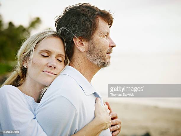Wife embracing husband on beach at sunset