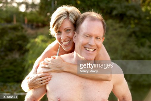 Wife hugging her husband from behind : Stock Photo