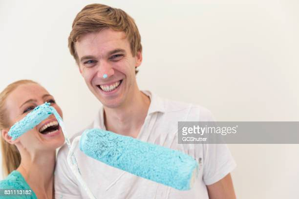 Wife laughing hysterically while holding a paint roller next to her husband