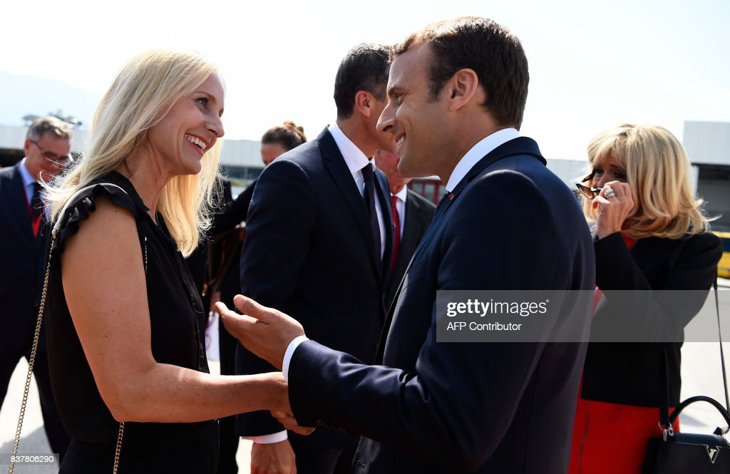 Wife of Austrian chancellor Eveline Steinberger-Kern greets French President Emmanuel Macron and Austrian chancellor Christian Kern (back C) greets wife of French President Brigitte Macron (R) upon arrival on August 23, 2017 at the airport in Salzburg. / AFP PHOTO / POOL / Bertrand GUAY