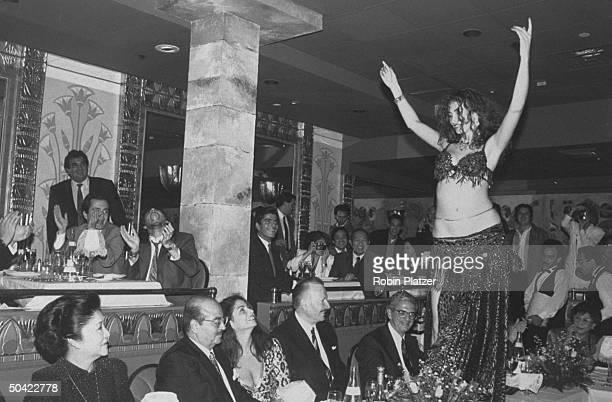 Wife of former Filipino Pres Imelda Marcos w Saudi arms dealer Adnan Khashoggi his daughter Nabila other guests watching belly dancer Nadia shimmying...